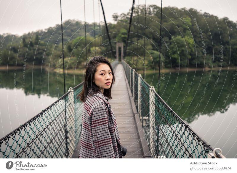 Ruhige asiatische Reisende auf Hängebrücke über Fluss stehend Tourist Suspension Brücke Wald Abenteuer Tourismus Urlaub malerisch friedlich Gelassenheit