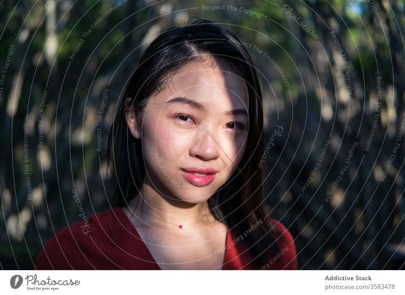 Verträumte junge Asiatin im Park stehend Frau nachdenken Windstille verträumt feminin Mund geöffnet Menschliches Gesicht Halskette ruhig Denken Gelassenheit
