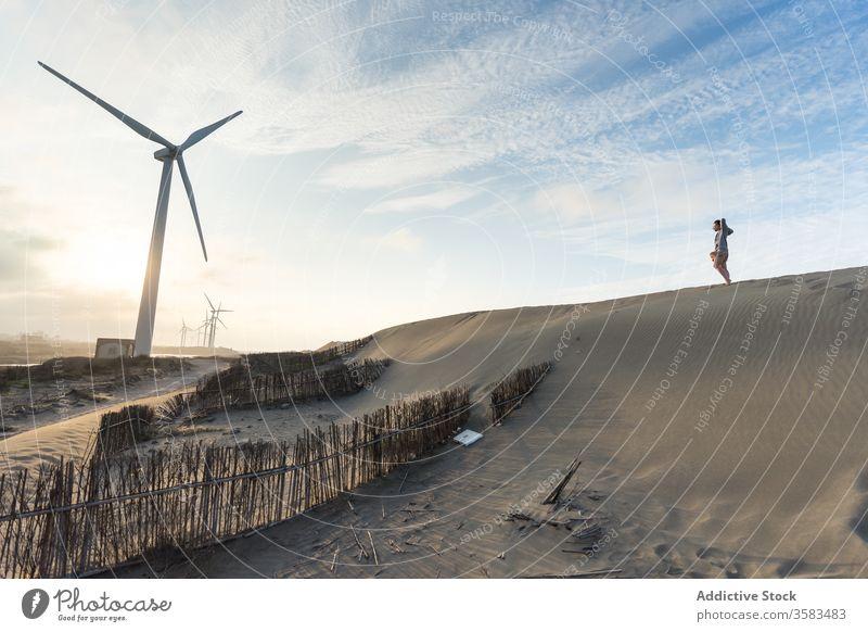 Unbekannter Reisender steht bei Sonnenuntergang auf Sandhügel nahe Windmühle Himmel Hügel Horizont Harmonie Landschaft malerisch Hügelseite erkunden Skyline
