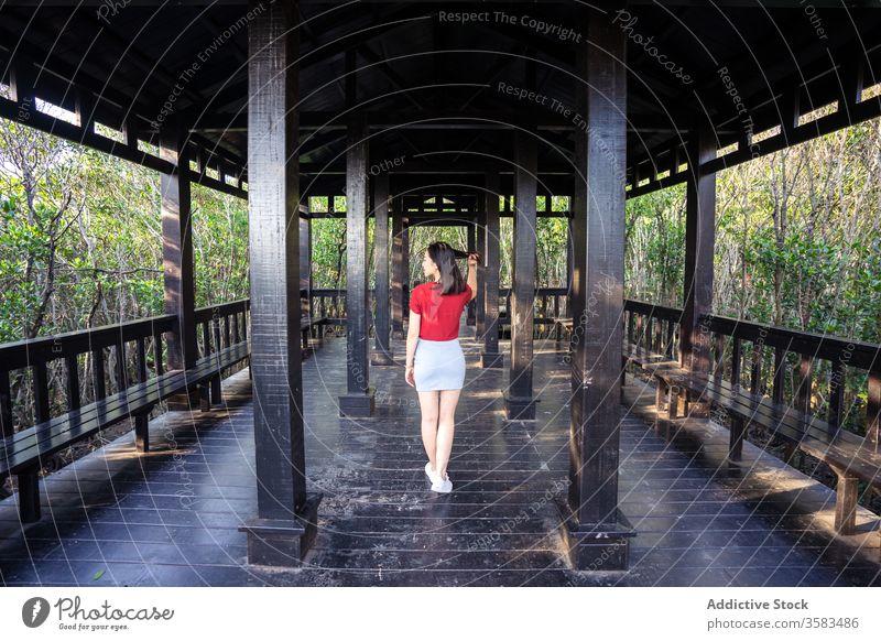 Asiatin auf Holzveranda im Wald bei Tageslicht stehend Frau Veranda Bank Spalte Architektur Haare berühren Freizeit Erholung Antiquität Gelassenheit hölzern