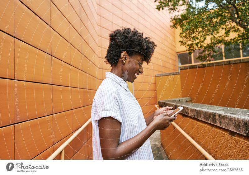 Glückliche schwarze Frau mit Smartphone auf der Straße gegen lebhaftes Äußeres eines modernen Gebäudes Nachrichtenübermittlung Weg Kälte Browsen verwenden