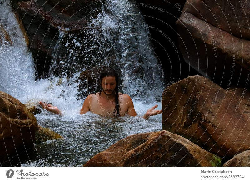 Meditation unter einem kaskadierenden Wasserfall Harmonie mit der Natur neues Zeitalter Wiedergeburt Kraft Kraft des Wassers Kraft der Natur