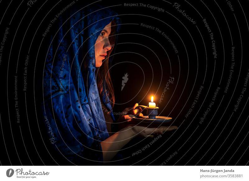 Traurige junge Frau mit Kerze und blauem Kopftuch Gesicht traurig schwarz Porträt frontal Profil ernst Kunst trist Leuchter Hände Flamme Brandwunde Licht