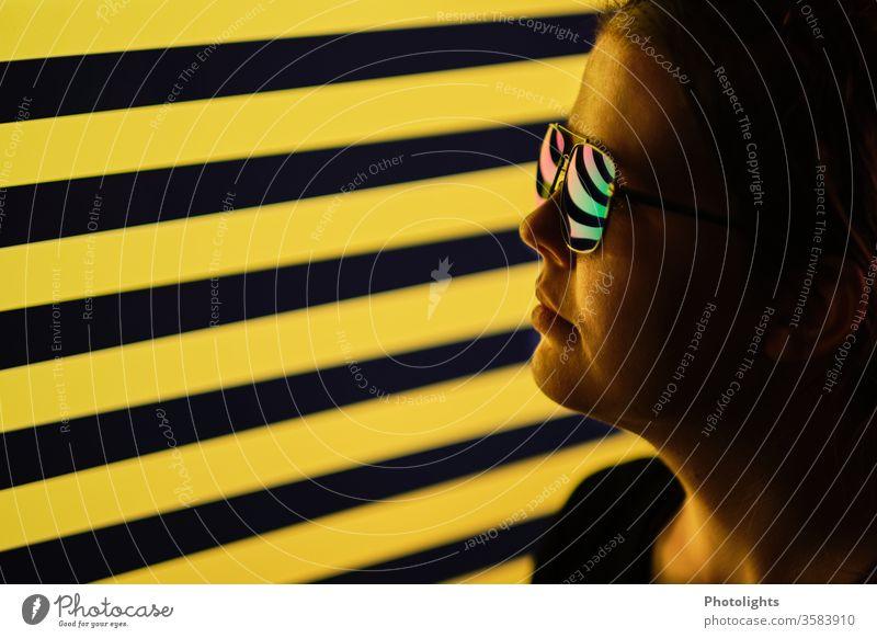 Frau mit spiegelnder Brille vor schwarz-gelben Hintergrund Stil Nase Profil Gesichtsausdruck Lippen Porträt Licht Blick Sonnenbrille Mensch