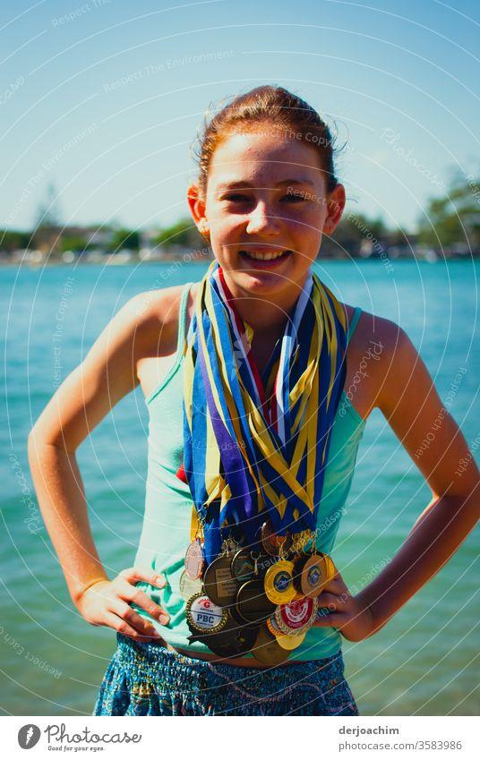 Mein Champion.//  Ein Mädchen steht fröhlich am Uferrand , lachend. Sie hat ganz viele Medallien um den Hals gehängt . Sie hat die Arme angewinckelt. girl