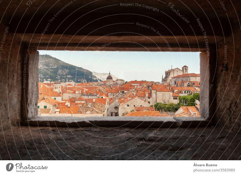 Orangefarbene Dächer von Dubrovnik, von der Wand aus gesehen, durch ein kleines Fenster, im Schatten der Nachmittagswolken, am Ufer der Adria. kleine Häuser