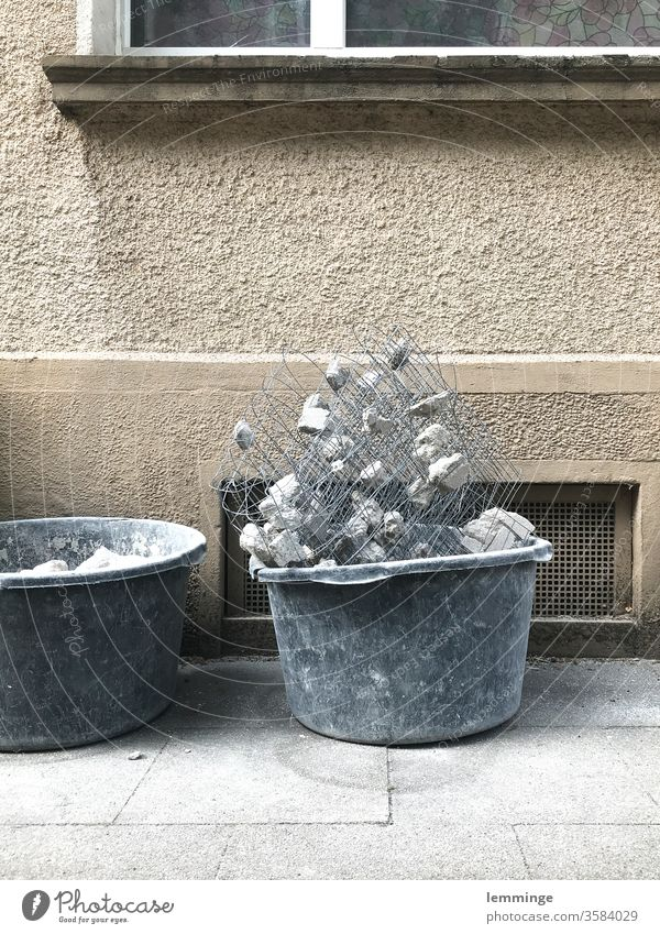 Eimer mit Bauschutt vor einer Fassade abrissreif Haus trist Abbruch schutthalde Mauerreste Wandel & Veränderung Zahn der Zeit schäbig Menschenleer Schutthaufen