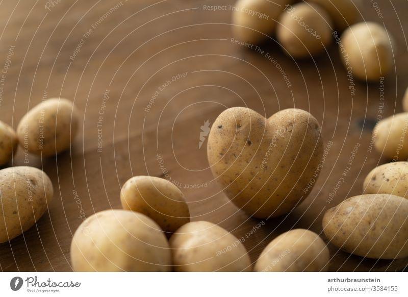 Frischer Kartoffel in Herzform auf braunem Holztisch Ernährung Essen Genuß Lebensmittel Nahrung Speise bio ernte gemüse gesund gesundheit hintergrund holz