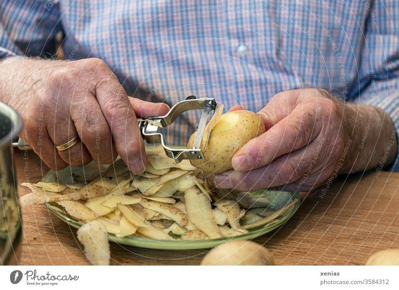 Senior in blau-karierten Hemd schält Kartoffeln am Tisch Hände Senioren schälen Schälmesser Teller Ehering Mann Lebensmittel Hand Ernährung Gemüse