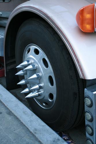 LKW-Radkappe mit Metallspitzen. Gesehen in den USA. Fotograf: Alexander Hauk Brummi Reifen Verkehr auto mobilität gefahr tüv blinker metall schwarz orange weiß