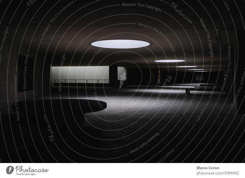 Sonnenlicht dringt durch Oberlichter auf dem Dach eines modernen Gebäudes ein. eine Person Silhouette Fahrrad gebaute Struktur Kontrast Architektur Stadtstraße