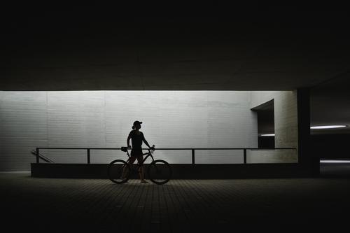 die Silhouette einer Person, die ihr Fahrrad durch die Straßen der Stadt schiebt eine Person gebaute Struktur Kontrast Architektur Stadtstraße Seitenansicht