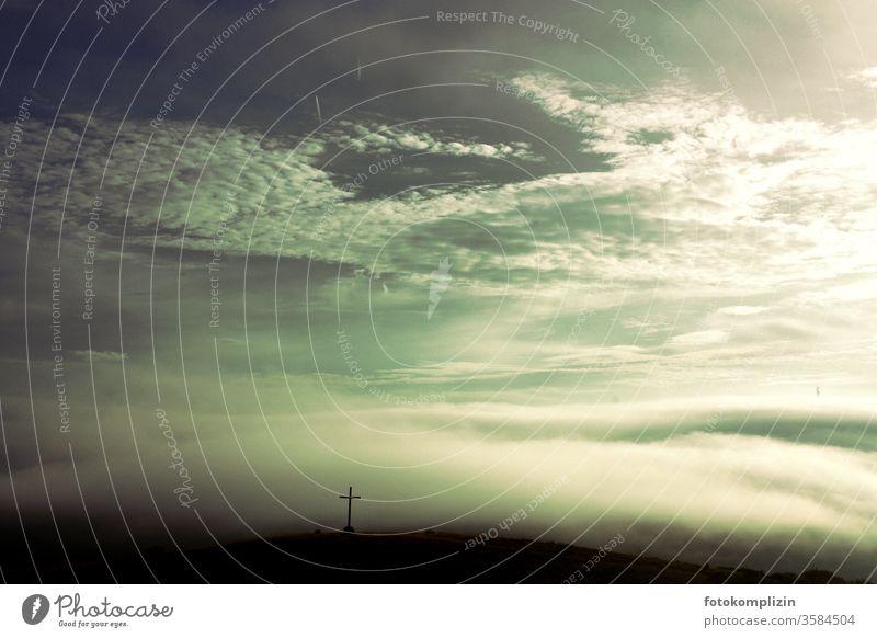 Kreuz auf einem Hügel in Nebel, Wolken und diffusem Licht Nebelstimmung Morgennebel Landschaft Nebelschleier Stimmung Morgendämmerung christlich Wetter