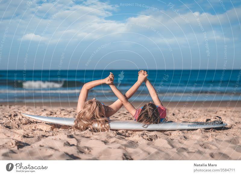 Zwei kleine Mädchen halten die Hände zusammen, die auf einem Surfbrett am Sandstrand des Ozeans liegen. Liebe, Freundschaft, Zusammengehörigkeitskonzept.