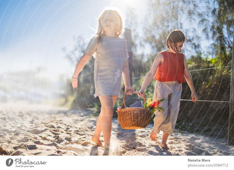 Kleine Mädchen, die barfuß über den Sand laufen und gemeinsam einen Picknickkorb pflegen. Sommerfreizeit, Liebe und Freundschaft. Natur Spaziergang Park Kind