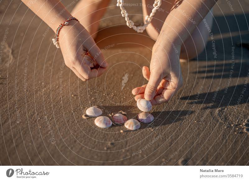 Kleine Mädchenhände, die am Sandstrand des Ozeans ein Herz aus Muscheln formen. Kind Hand Liebe Meeresufer Panzer Sommer Sonne im Freien Natur Lifestyle