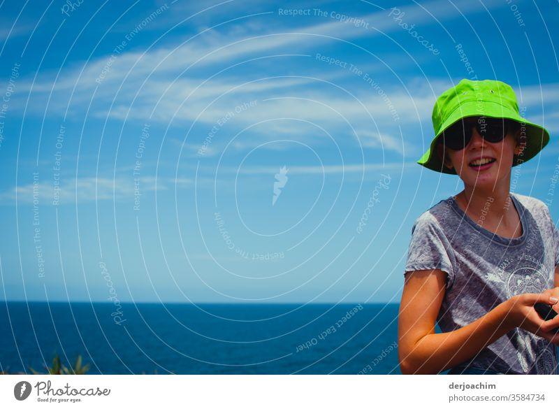 """Der """" Neue """" Hut steht mir gut. Ein Mädchen mit neuen Hut in  Grün,   steht am Meeres Strand. Im Hintergrund der Pacific. Girls hut Nahaufnahme girls schön"""