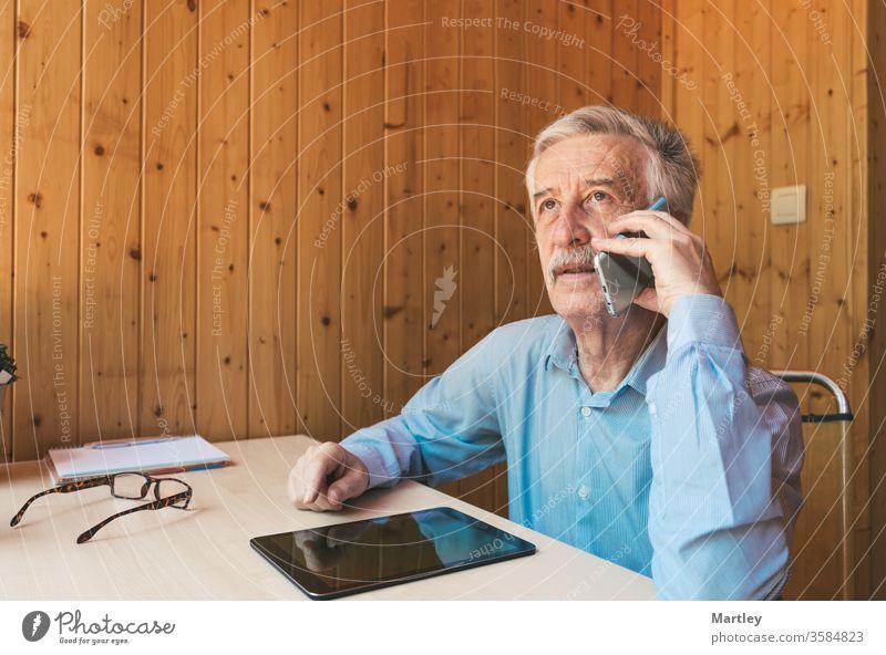 Großvater im Gespräch mit seinen Enkeln und Verwandten, die von zu Hause unter Quarantäne gestellt wurden, über das Coronavirus. Älterer Mann benutzt Smartphone und Tablet in seinem Büro