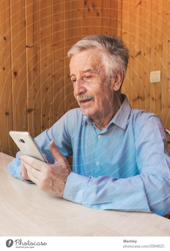 Glücklicher grauhaariger älterer Mann, der ein Smartphone benutzt und während des Coronavirus einen Videoanruf bei seinen Enkelkindern oder seiner Familie zu Hause tätigt. Er schaut sich lustige Videos in sozialen Netzwerken an.