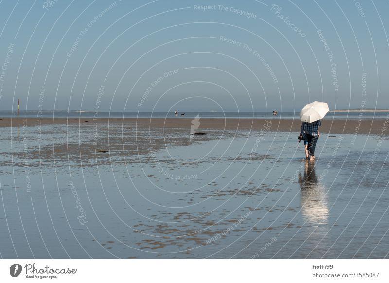 Wandern im Watt bei Ebbe mit Sonnenschirm Schirm gehen 1 Mensch Wattenmeer Meer Bewegung hell maritim nass Nordsee Küste Wege & Pfade Erholung Einsamkeit