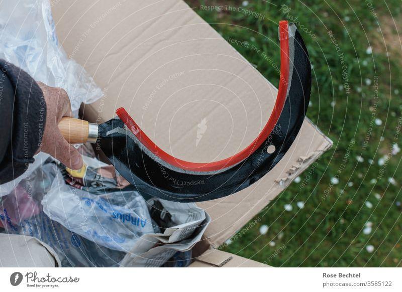 Hand mit Sichel Paket Wiese Verpackung Farbfoto Menschenleer Nahaufnahme Textfreiraum oben Textfreiraum rechts objekt der begierde auspacken