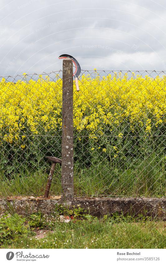 Hammer und Sichel am Zaun hammer und sichel Symbole & Metaphern Werkzeug Maschendrahtzaun Grenze alt schief Raps Rapsfeld Handwerk Zeichen objekt der begierde