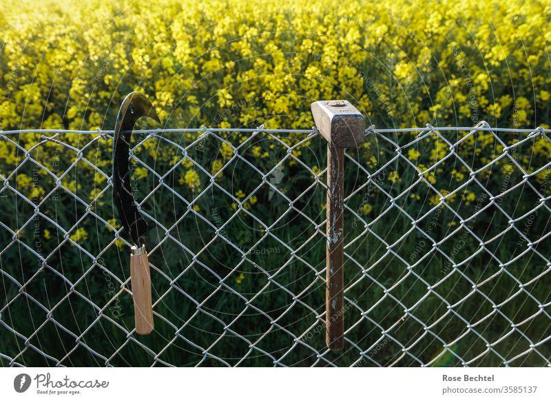Hammer und Sichel am Feldzaun hammer und sichel Werkzeug Zaun Maschendrahtzaun Grenze Raps Rapsfeld Handwerk alt objekt der begierde Symbole & Metaphern gerade