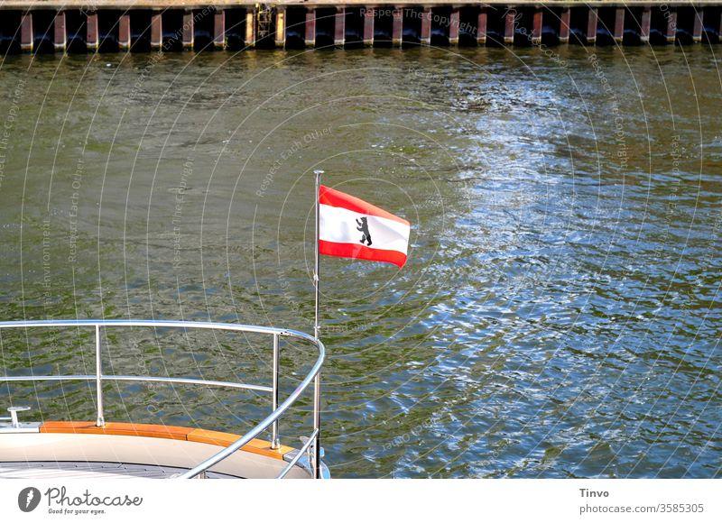 Landesflagge Berliner Bär an der Reling eines Schiffes Flagge Spree Schifffahrt Tourismus Kaimauer Schiffsbug Wappentier weiß rot gestreift Textfreiraum Wasser