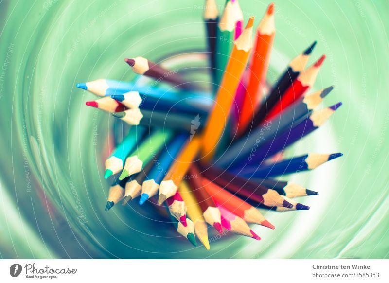 kunterbunte Buntstifte von oben gesehen in einem grünen Wirbel bunt gemischt Stifte Spitzen malen zeichnen Kindergarten Grundschule Schule Farbstift