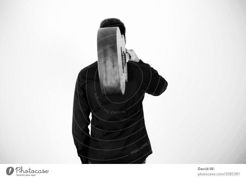 Mann der eine Gitarre trägt Musiker Konzert coronavirus verbot Künstler Schwarzweißfoto anonym Musikinstrument Musik hören Auszeit Pause geschlossen Kunst