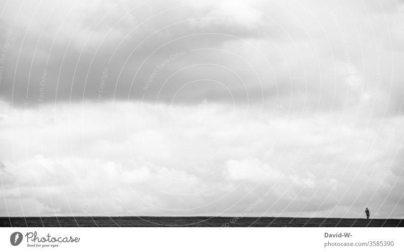 Mann spaziert in der Ferne über einen Deich spazieren spazierengehen Urlaub ruhe auszeit alleine Ruhe vor dem Sturm wolken Himmel Miniatur klein