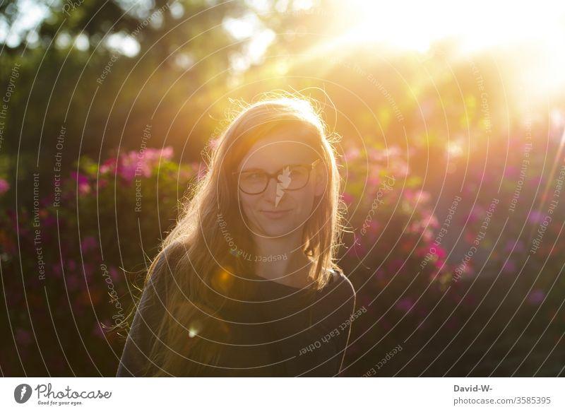 Frau mit Brille im Sonnenschein und Gegenlicht Junge Frau sonnenstrahlen natürlich Erwachsene Farbfoto Sonnenstrahlen 1 Sonnenlicht 18-30 Jahre Außenaufnahme