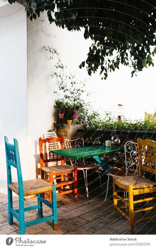 Malerischer Tisch mit Stühlen auf Terrasse mit Grünpflanzen Landschaft Haus Veranda farbenfroh Stuhl Metall Zaun Efeu heimwärts Cottage Gebäude Außenseite
