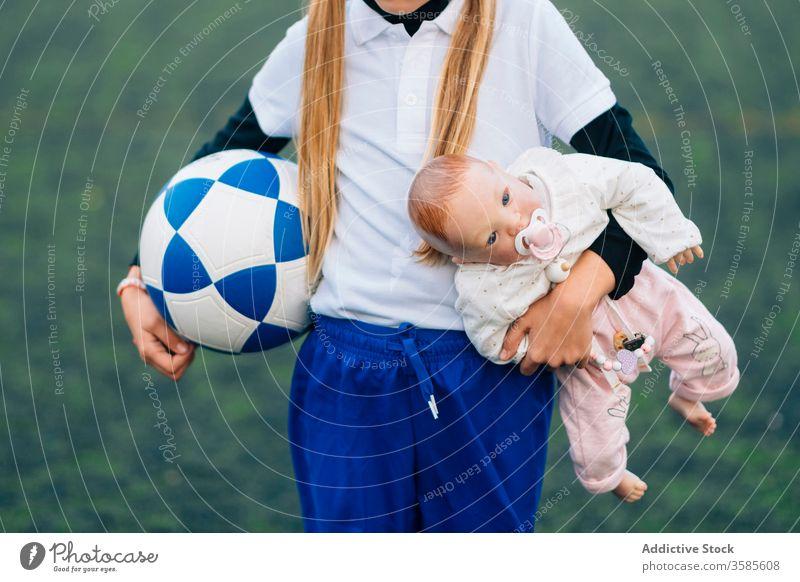 Erntedankfestes Mädchen mit Fussball und Puppe auf dem Feld Fußball Wahl Kind Stereotyp Sport Ball Konzept Uniform Spiel Spielzeug Training Gerät Trikot Spieler