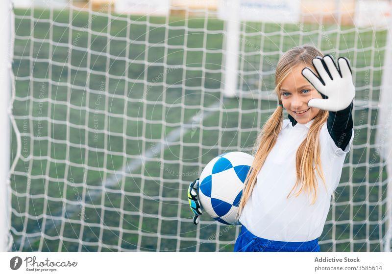 Glückliche junge Spielerin mit Ball in Fussballarena im Sportstadion Mädchen Fußball Feld Uniform Kind Club Kindheit Athlet Gerät Lächeln Schulmädchen heiter