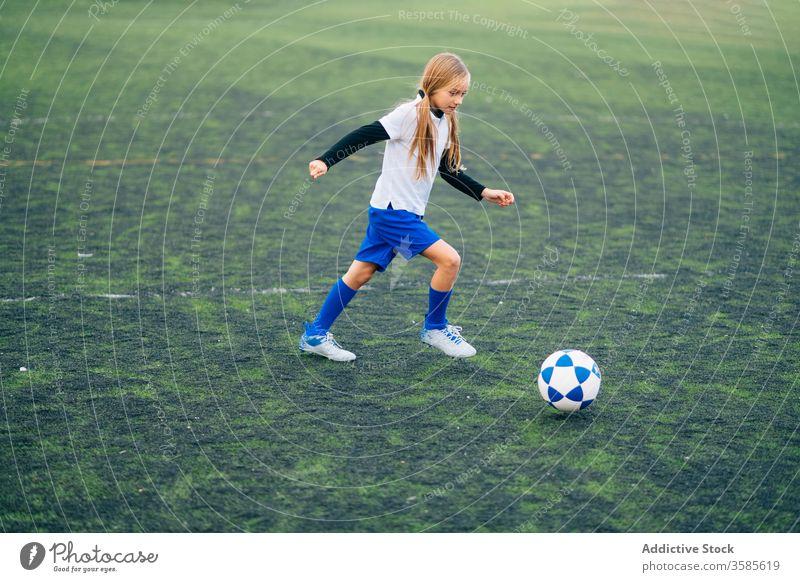 Fokussierte junge Spielerin, die im Sportstadion Fussball spielt Mädchen Fußball Ball Feld Kind laufen spielen Uniform Club Training Aktivität Stadion Athlet