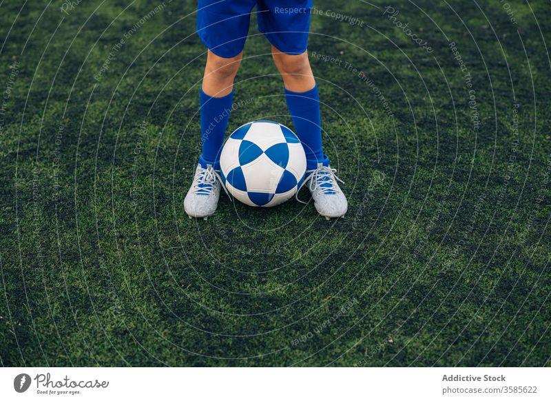 Kornkind in blauer Uniform mit Fussball auf grünem Feld im zeitgenössischen Sportverein Kind Ball Fußball Spieler Bein Klampen Club Gericht Stadion Training