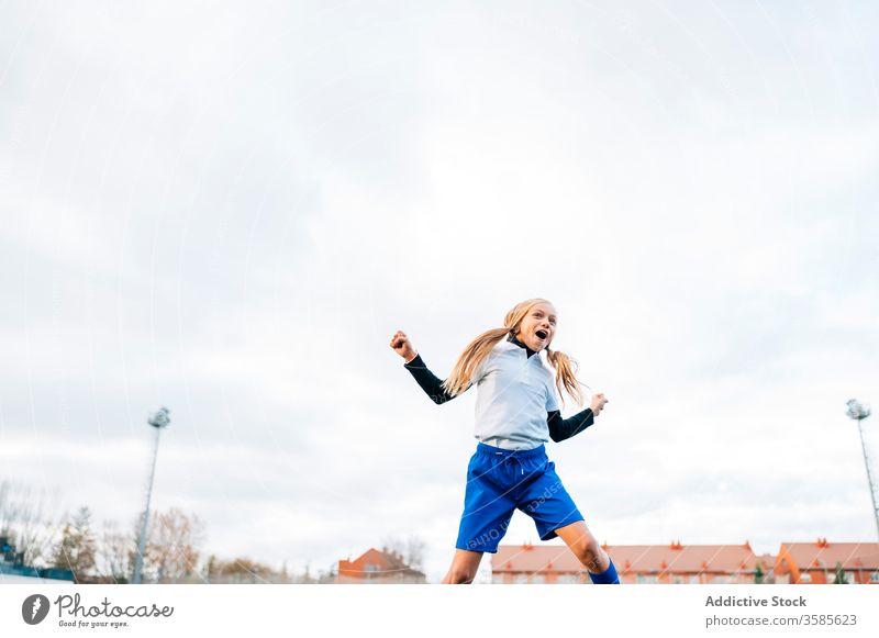 Fröhliche junge Spielerin freut sich über den Erfolg beim Fussballspielen im Sportstadion Mädchen Fußball gewinnen Kind Ball feiern Tor Sieg Glück Feld Triumph