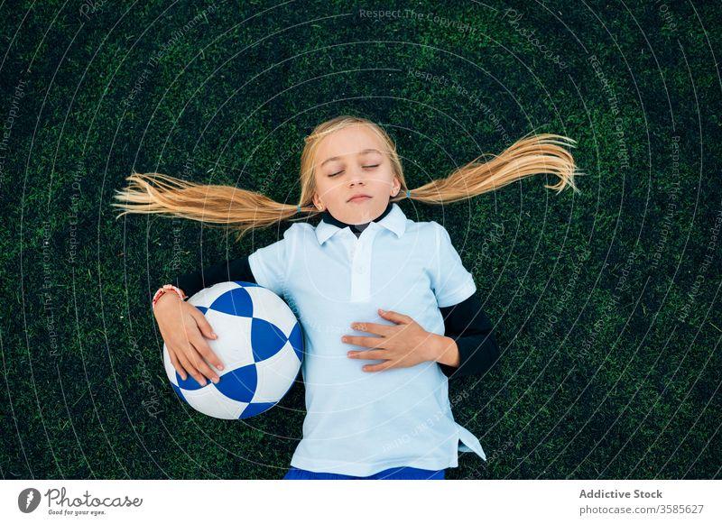 Fröhliche Spielerin mit Fussball entspannt auf dem Rasen Mädchen Fußball Lachen Feld sich[Akk] entspannen Ball Pferdeschwanz Stadion Kind Glück spielerisch