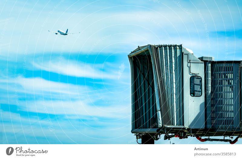 Jet-Brücke nach dem Start der Verkehrsfluggesellschaft auf dem Flughafen und dem Flugzeug, das im blauen Himmel und in weißen Wolken fliegt. Flugzeug-Fluggastbrücke angedockt. Abflug der internationalen Fluggesellschaft.