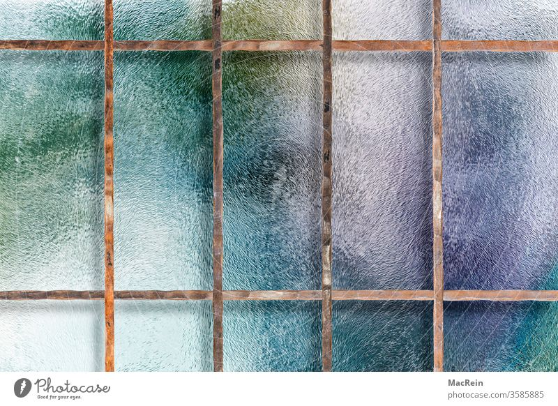 Vergittertes Fenster buntes glas fenster fensterscheibe fensterglas fenstergitter absichern geschützt schutz rost rostig verstrebung farbige spiegelung
