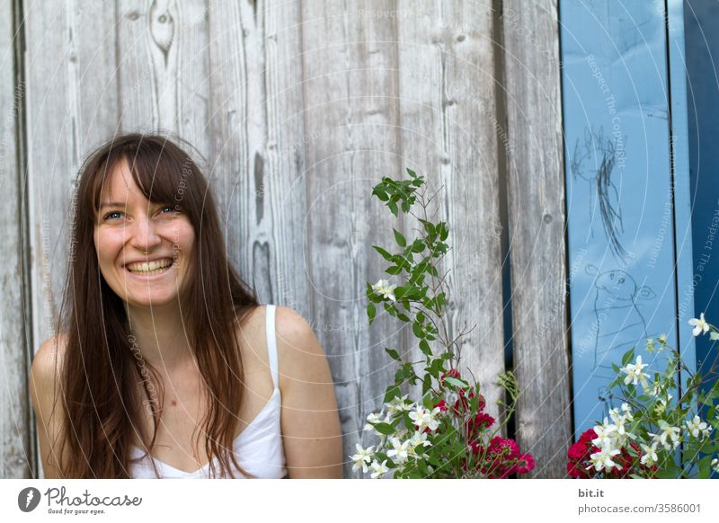 Lachende, langhaarige junge Frau sitzt vor einer alten Holzwand draussen im Garten und freut sich über Blumen-Geschenk von Partygast. Fröhliche, natürliche, brünette junge Erwachsene mit strahlendem Gesicht auf Gartenparty Fest in Partylaune lacht freudig.