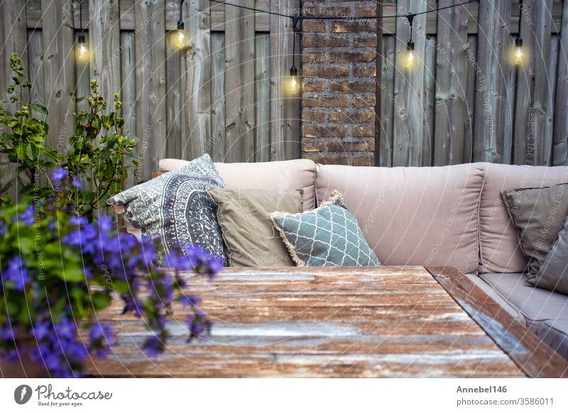 Stilvolle Gartenmöbel im Freien, Sofa mit Kissen und Lampen, hängende Glühbirnen, gemütliche moderne Ecke auf der Terrasse Blume Hintergrund Familie Spa Design