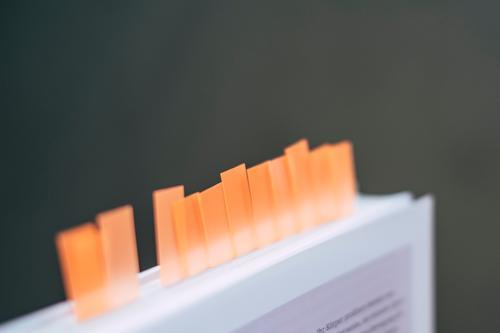 Ein Buch mit vielen Haftmarkern und Sticky Notes um Seiten zu markieren unübersichtlich Page Marker Notizen orange Bildung hervorheben Literatur Erinnerung
