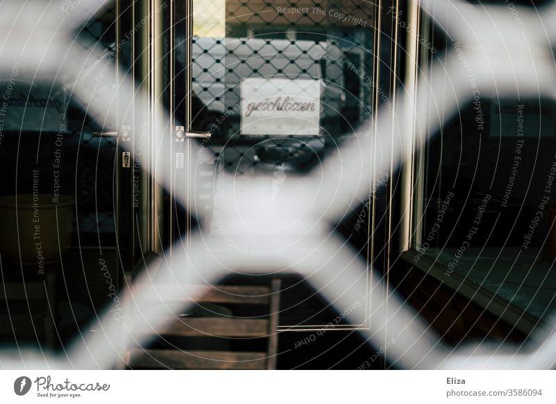 Die vergitterte Tür eines Geschäfts, an dem ein geschlossen Schild hängt Einzelhandel Wirtschaft Laden Krise bankrott Insolvenz geschäftsaufgabe corona