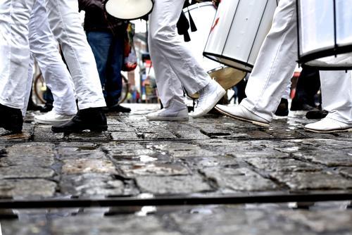 schwarz weiß gekleidete Menschen gehen über Kopfsteinpflaster - es hat geregnet aber der Zug setzt sich fort Beine Kleidung marschieren Trommel Marschformation