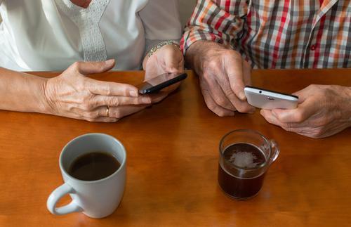 Draufsicht auf alte Menschen, die zu Hause Smartphones benutzen, während sie Tassen mit heißen Getränken genießen. Konzept von älteren Menschen und Technik.