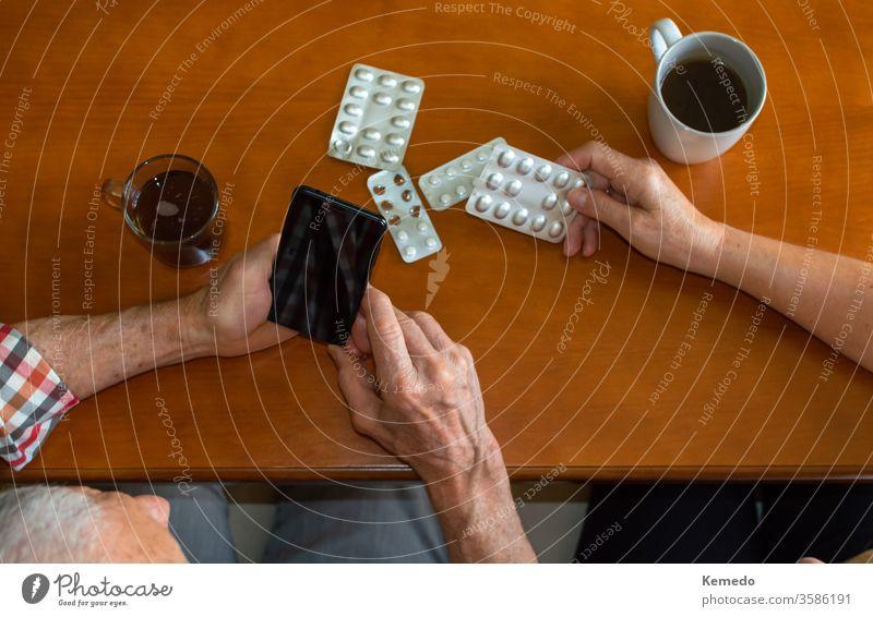 Top-Ansichten von älteren Menschen, die Mobiltelefone benutzen, um zu Hause bei heißen Getränken medizinische Fragen zu beantworten. Ältere Menschen und die Nutzung von Technologie aus medizinischen Gründen.