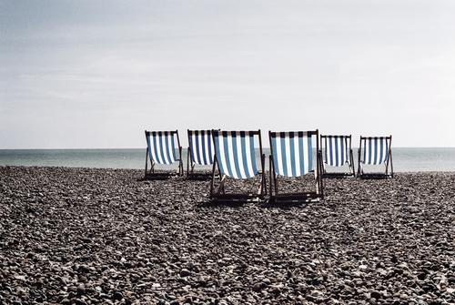 Blau gestreifte Liegestühle an einem britischen Kieselstrand Brighton Großbritannien Niemand leer niemand Miete vereinigtes königreich Küstenstreifen Wasser
