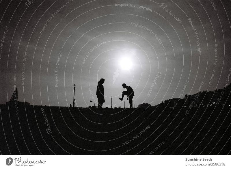 Zwei Jungs spielen Hacky Sack in einem Park bei Sonnenuntergang in Brighton Uk im Freien abgelegt Ball Hippie Jungen Erholung Abenddämmerung Menschengruppe jung